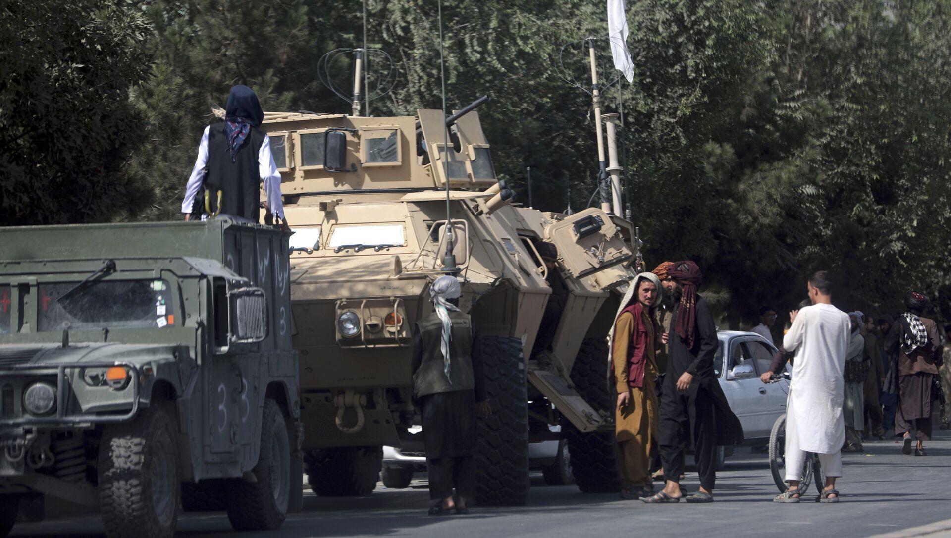 Các chiến binh Taliban đứng gác trên đường tới Sân bay Quốc tế Hamid Karzai, ở Kabul, Afghanistan, Thứ Hai, ngày 16 tháng 8 năm 2021 - Sputnik Việt Nam, 1920, 18.08.2021