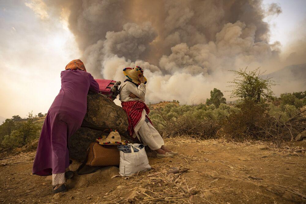Các phụ nữ và vật dụng trên con đường núi trong vụ cháy rừng ở miền bắc Maroc