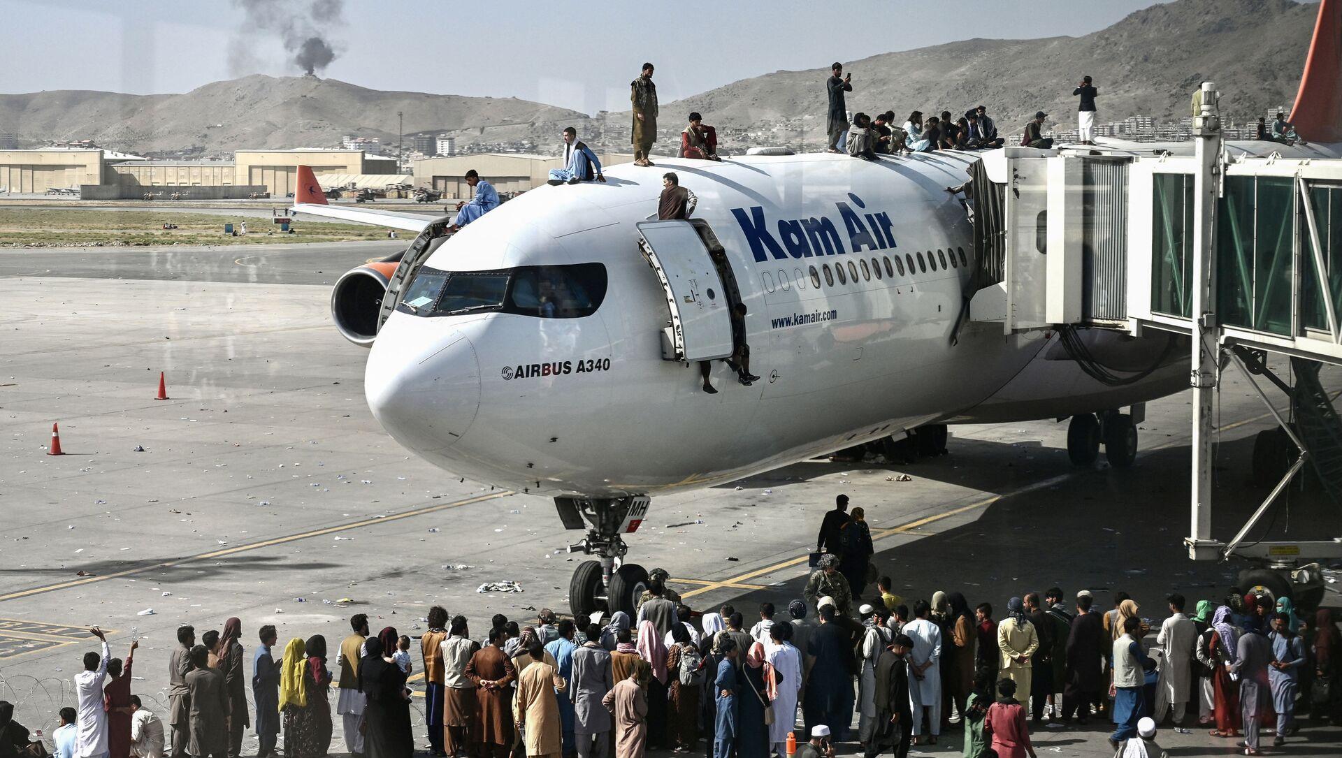 Người Afghanistan leo lên máy bay tại sân bay sau khi Taliban tiến vào Kabul - Sputnik Việt Nam, 1920, 30.08.2021