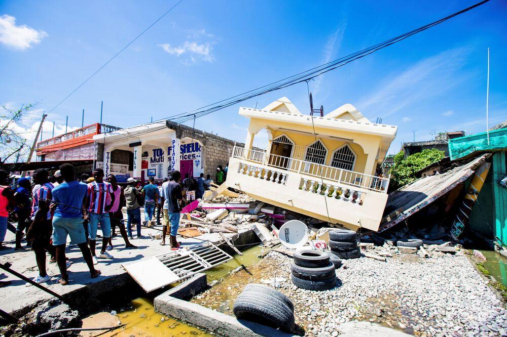 Người dân cạnh ngôi nhà bị phá hủy bởi trận động đất 7,2 độ richter ở Le Quay, Haiti