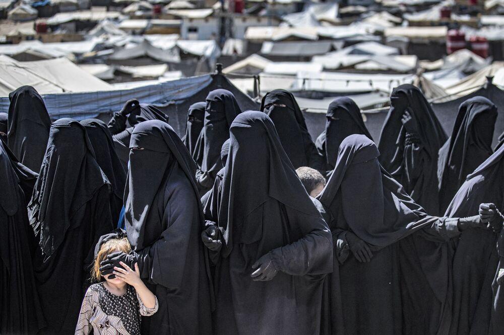 Các phụ nữ với con nhỏ xếp hàng nhận gói viện trợ nhân đạo tại trại Al-Hol, nơi tạm giữ thân nhân chiến binh IS* ở tỉnh Hasakeh của Syria