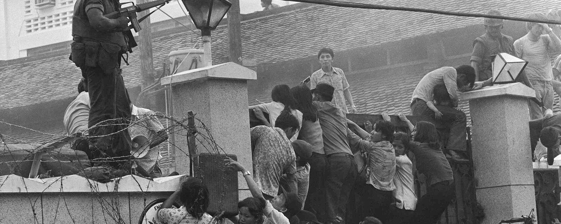 People clamber into the US embassy compound during the fall of Saigon in 1975 - Sputnik Việt Nam, 1920, 21.08.2021