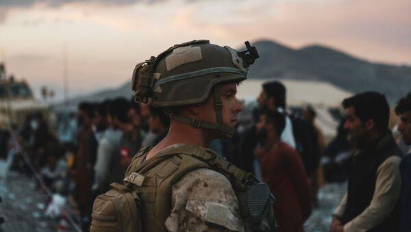 Một lính thủy đánh bộ được phân công cho Lực lượng Đặc nhiệm Mặt đất trên Không-Đối phó Khủng hoảng-Bộ Tư lệnh Trung tâm hỗ trợ người sơ tán trong cuộc sơ tán tại Sân bay Quốc tế Hamid Karzai, ở Kabul, Afghanistan, ngày 20 tháng 8 năm 2021. - Sputnik Việt Nam
