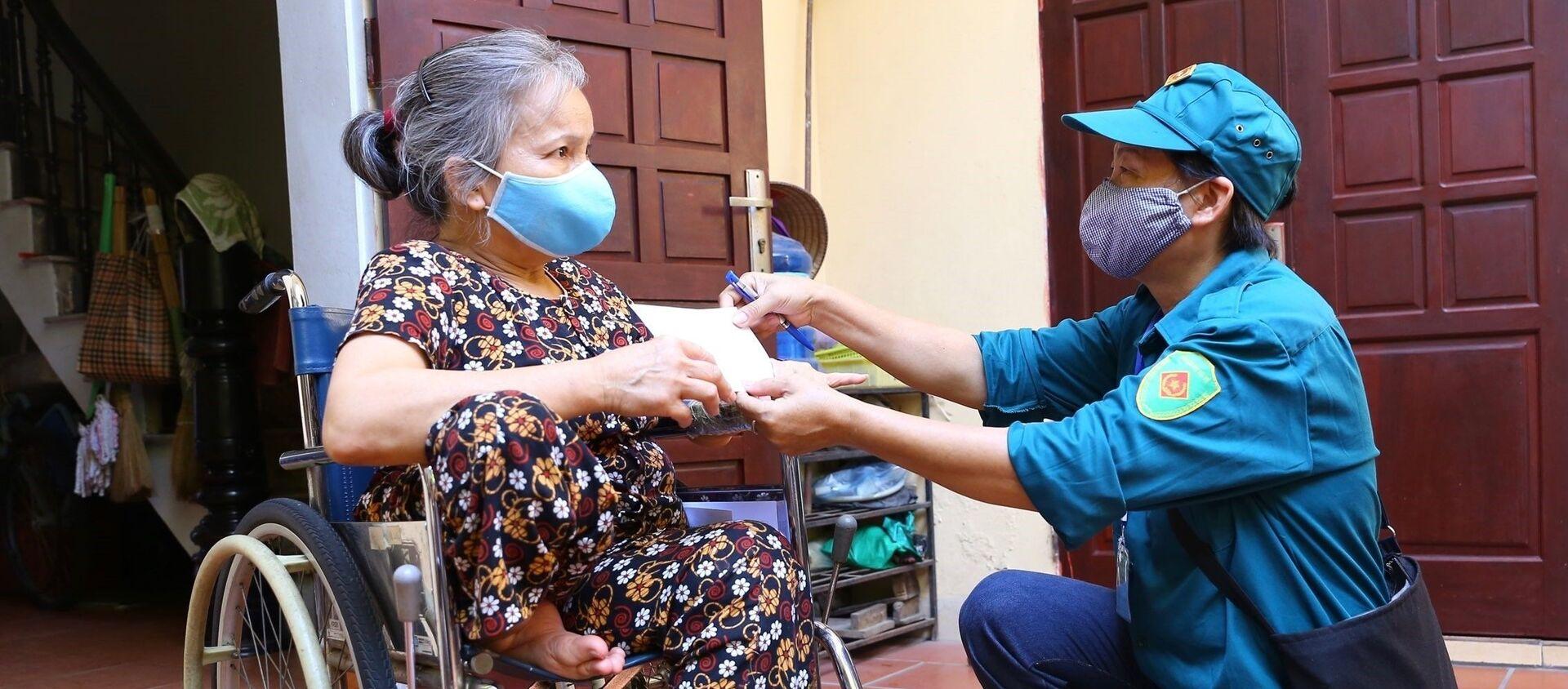Bà Đỗ Thị Tâm, người khuyết tật ở tổ dân phố 5, phường Phú La, quận Hà Đông là một trong 3.791 người thuộc diện bảo trợ xã hội được nhận hỗ trợ, sáng 18/8 - Sputnik Việt Nam, 1920, 22.08.2021