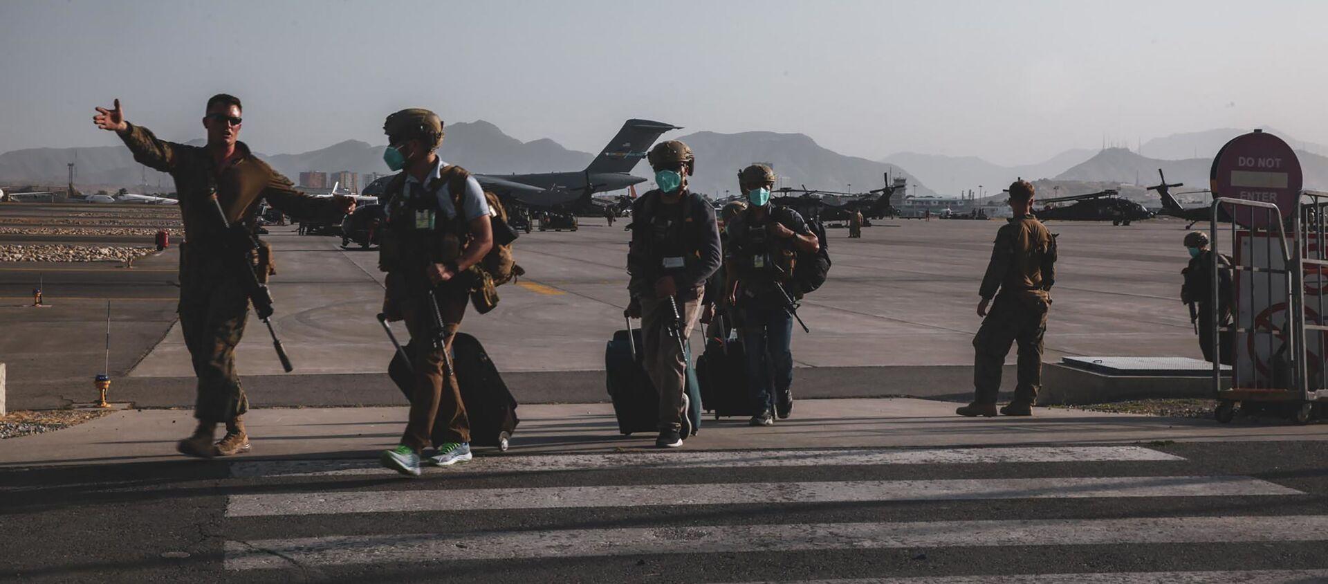 Một lính thủy đánh bộ thuộc Hải đội Viễn chinh Thủy quân lục chiến số 24 tháp tùng các nhân viên Bộ Ngoại giao chuẩn bị sơ tán tại Sân bay Quốc tế Hamid Karzai ở Kabul, Afghanistan. - Sputnik Việt Nam, 1920, 24.08.2021