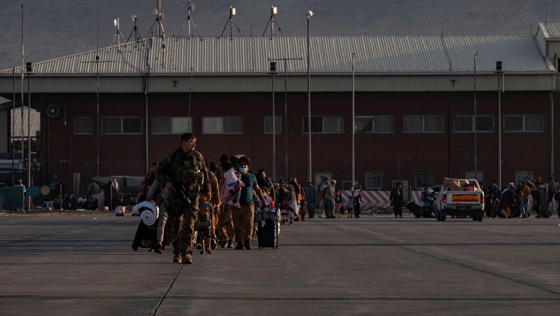 Phi công của Lực lượng Không quân Hoa Kỳ dẫn những người sơ tán lên máy bay C-17 Globemaster Lực lượng Không quân Hoa Kỳ III tại sân bay quốc tế Hamid Karzai (HKIA), Afghanistan, 24/8/2021 - Sputnik Việt Nam, 1920, 25.08.2021