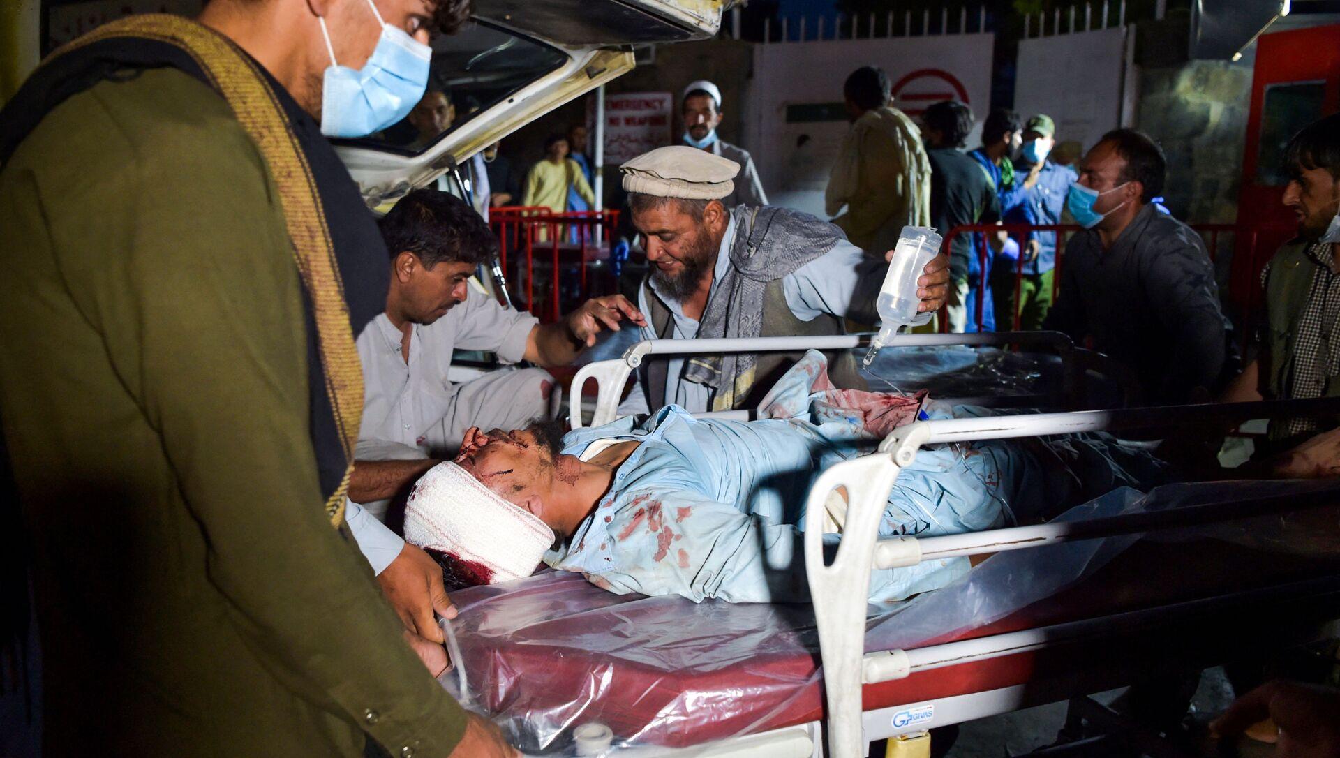 Nhân viên y tế đang khiêng một người đàn ông bị thương trên cáng để hỗ trợ y tế sau hai vụ nổ ở sân bay Kabul - Sputnik Việt Nam, 1920, 26.08.2021