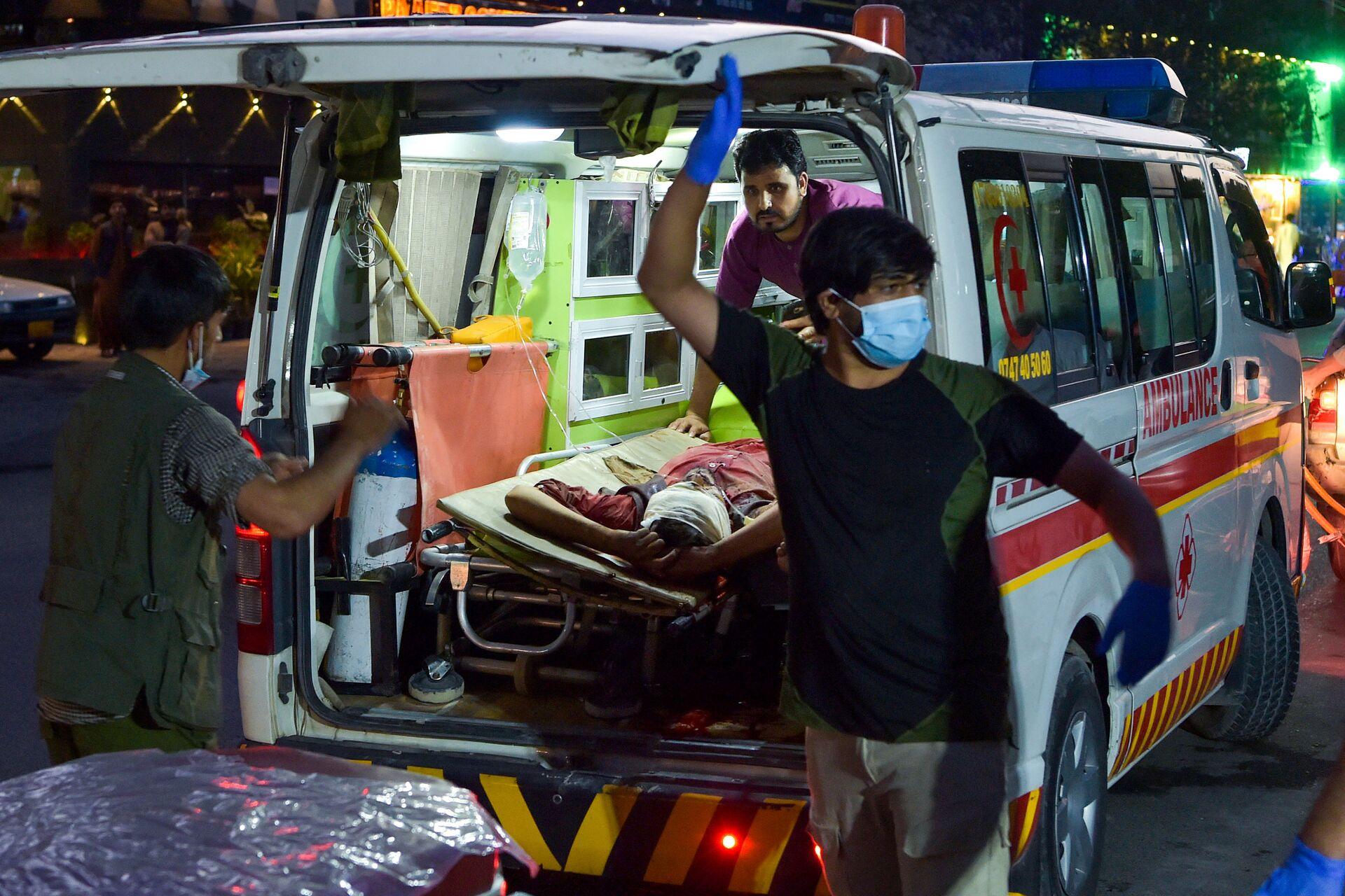 Các nhân viên y tế đang giúp đỡ những người bị thương sau hai vụ nổ lớn xảy ra ở Kabul - Sputnik Việt Nam, 1920, 05.10.2021