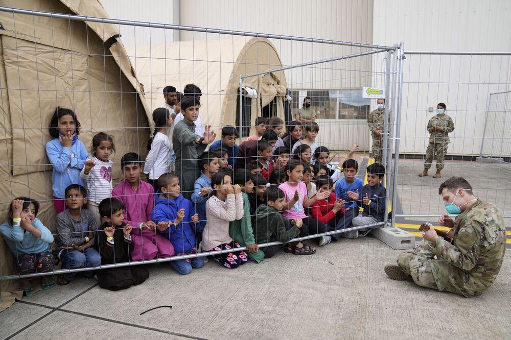 Người lính Mỹ chơi guitar cho trẻ em Afghanistan vừa sơ tán tại căn cứ không quân Ramstein, Đức