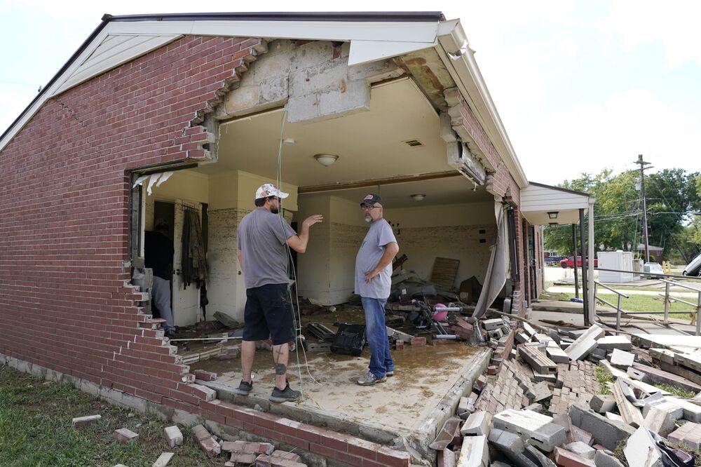 Brian Mitchell (phải) nhìn ngôi nhà bị phá hủy của mẹ vợ với người bạn của gia đình Chris Hoover,  bang Tennessee