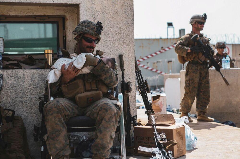 Lính thủy đánh bộ Mỹ bế em bé trên tay trong cuộc sơ tán tại sân bay quốc tế ở Kabul, Afghanistan