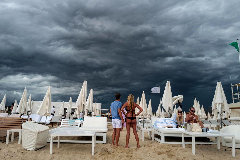 Mọi người nhìn mây đen trên bãi biển ở Ramatuelle, gần Saint-Tropez, miền nam nước Pháp