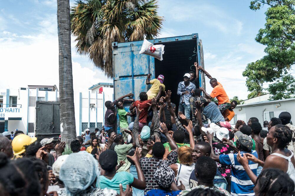 Người đàn ông ném bao gạo vào đám đông khi đang phân phát thức ăn và nước uống cho các nạn nhân động đất ở Le Quay, Haiti
