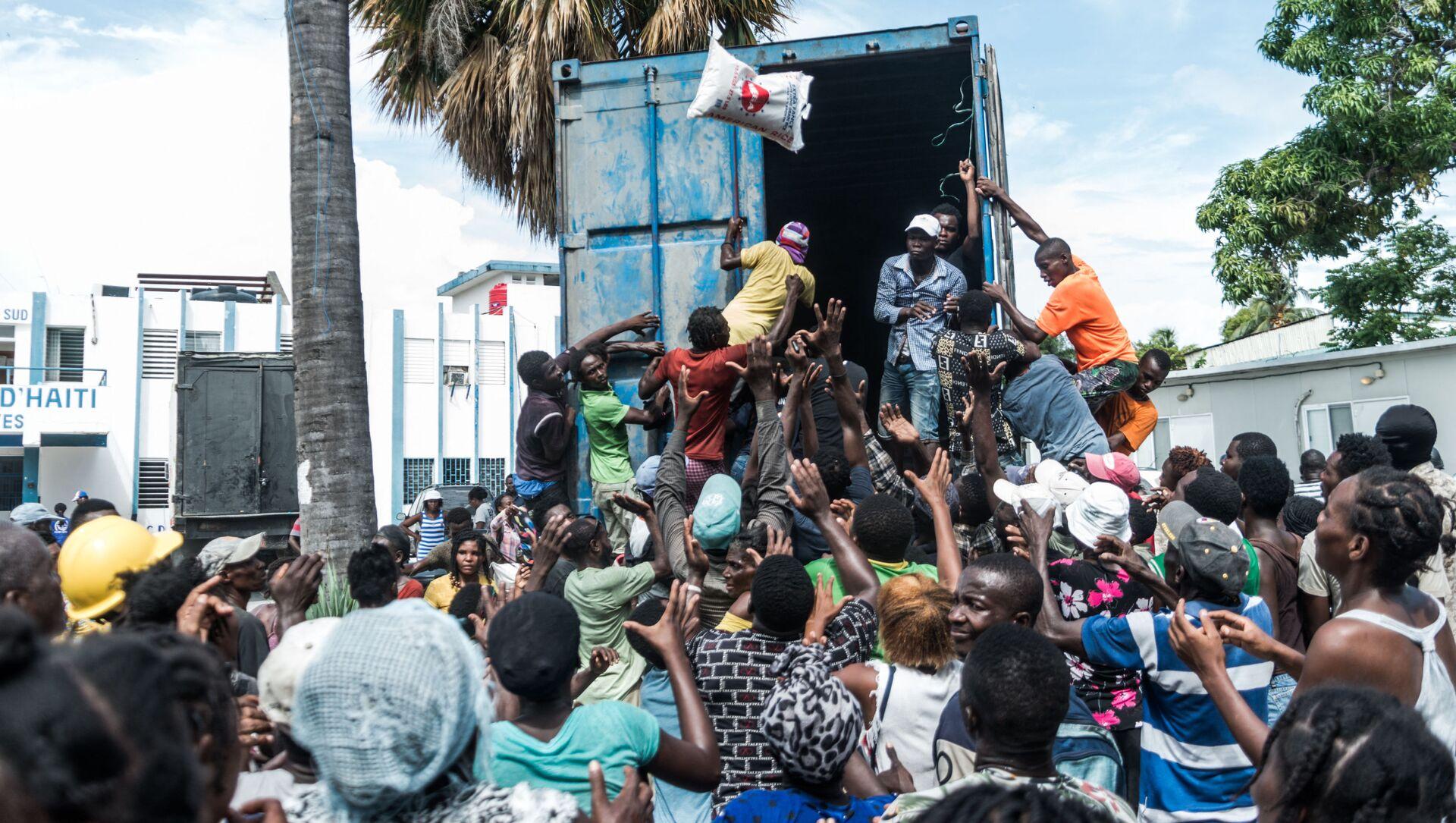 Người đàn ông ném bao gạo vào đám đông khi đang phân phát thức ăn và nước uống cho các nạn nhân động đất ở Le Quay, Haiti - Sputnik Việt Nam, 1920, 20.09.2021