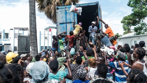 Người đàn ông ném bao gạo vào đám đông khi đang phân phát thức ăn và nước uống cho các nạn nhân động đất ở Le Quay, Haiti - Sputnik Việt Nam