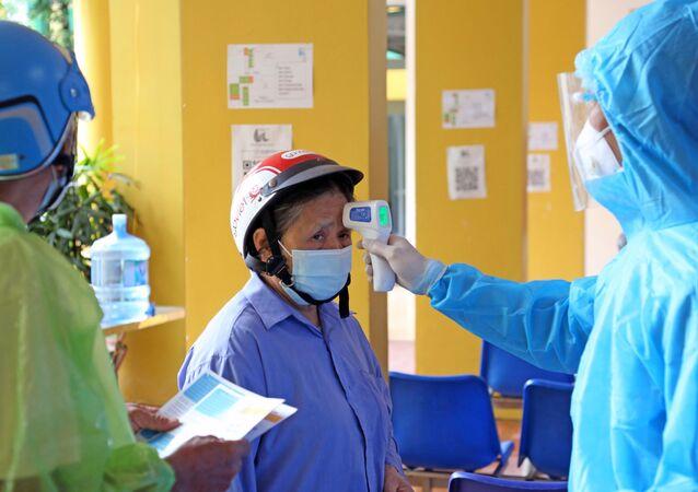 Đo thân nhiệt cho nhân dân đến tiêm vaccine tại bệnh viện Dệt may.