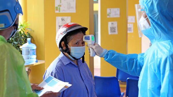 Đo thân nhiệt cho nhân dân đến tiêm vaccine tại bệnh viện Dệt may. - Sputnik Việt Nam