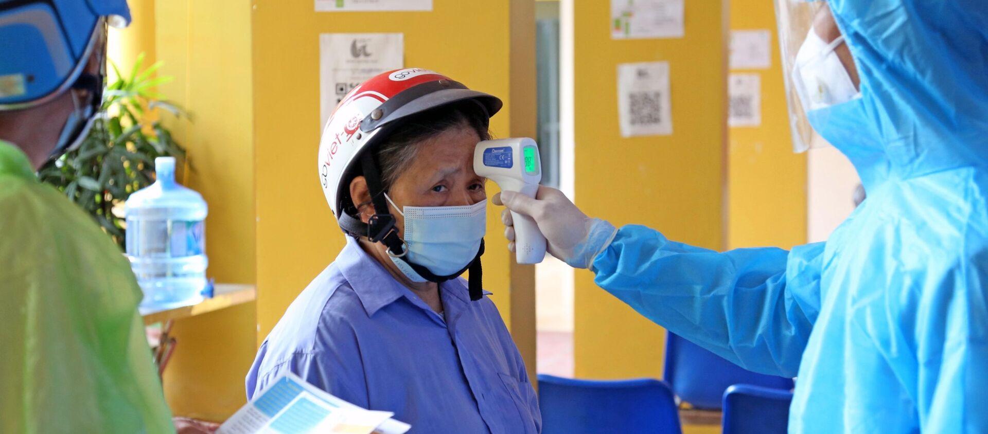 Đo thân nhiệt cho nhân dân đến tiêm vaccine tại bệnh viện Dệt may. - Sputnik Việt Nam, 1920, 13.09.2021