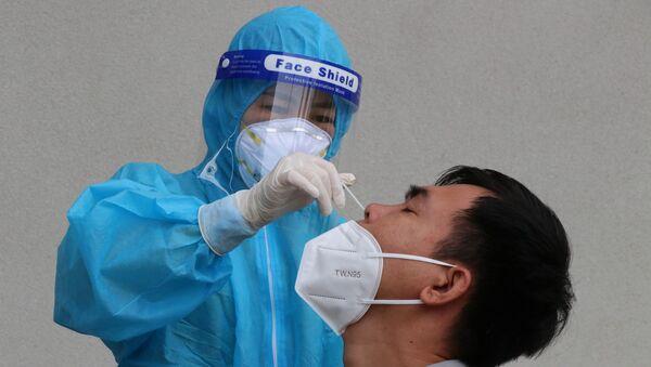Lực lượng y tế làm test nhanh xét nghiệm COVID-19 cho người dân tại thành phố Thủ Dầu Một, tỉnh Bình Dương. - Sputnik Việt Nam