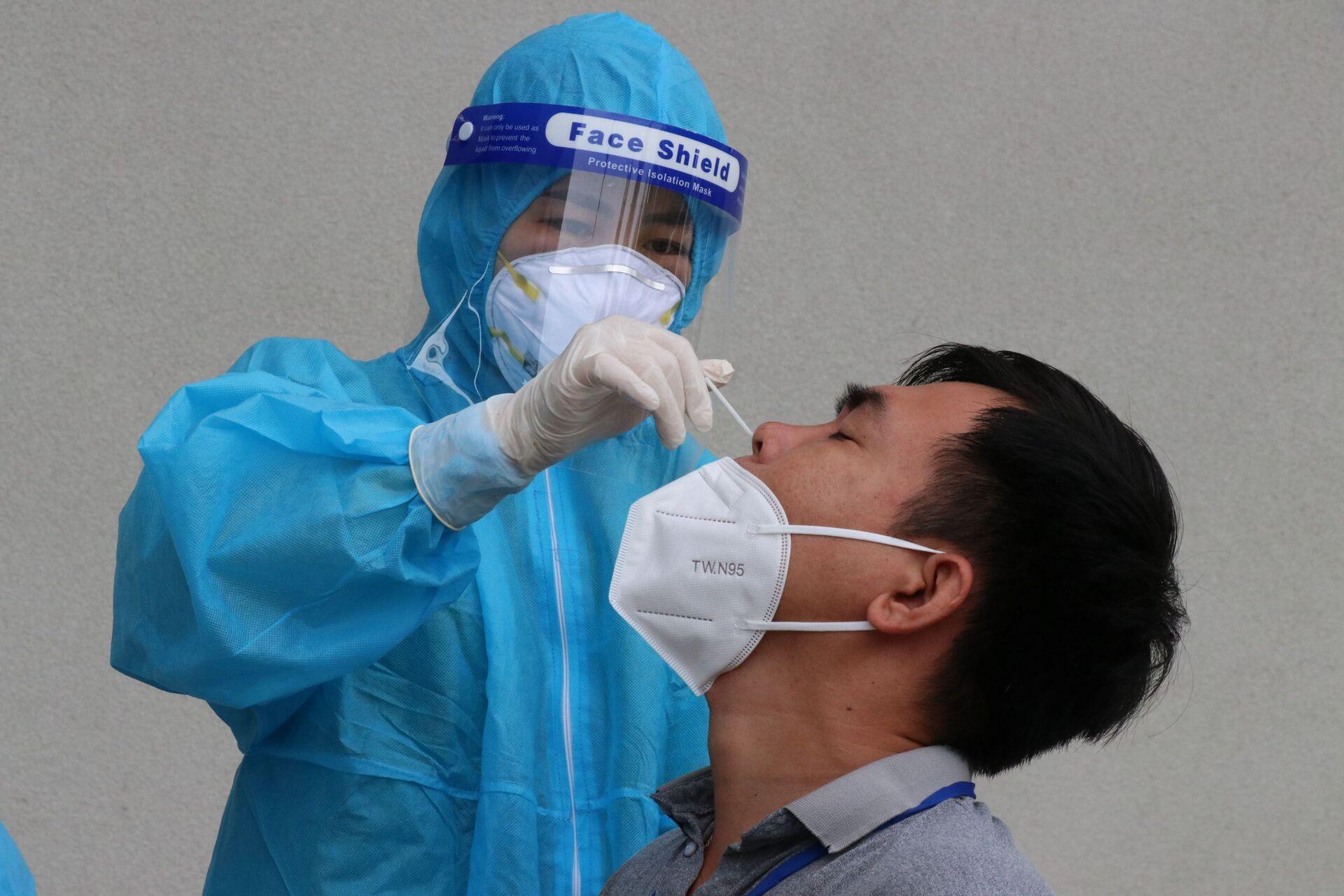 Lực lượng y tế làm test nhanh xét nghiệm COVID-19 cho người dân tại thành phố Thủ Dầu Một, tỉnh Bình Dương. - Sputnik Việt Nam, 1920, 05.10.2021