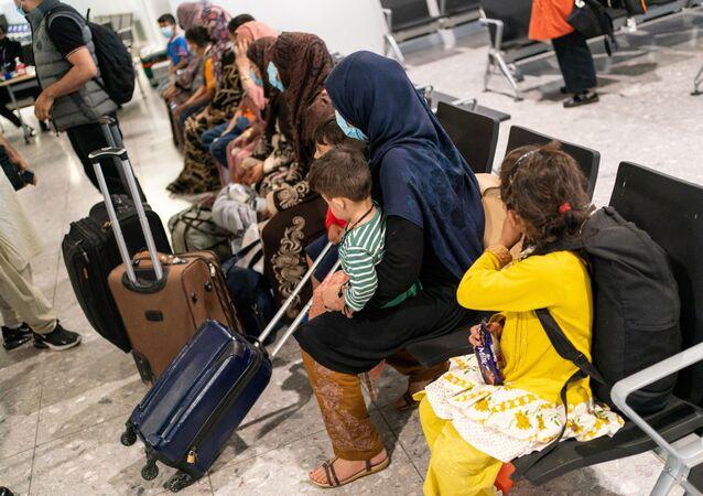 Những người tị nạn từ Afghanistan chờ được xử lý sau khi đáp chuyến bay sơ tán tại sân bay Heathrow, ở London, Anh ngày 26 tháng 8 năm 2021