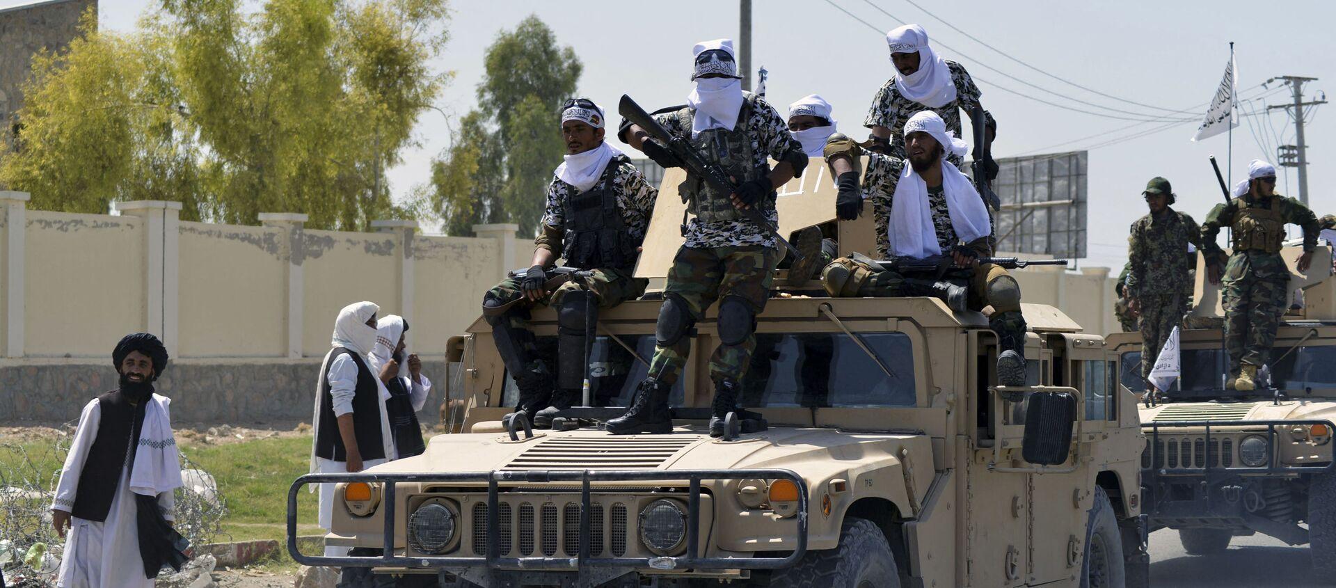 Các chiến binh Taliban trên đỉnh xe Humvee diễu hành dọc theo con đường để ăn mừng sau khi Mỹ rút hết quân khỏi Afghanistan, tại Kandahar vào ngày 1 tháng 9 năm 2021 sau khi quân đội Taliban tiếp quản đất nước - Sputnik Việt Nam, 1920, 02.09.2021