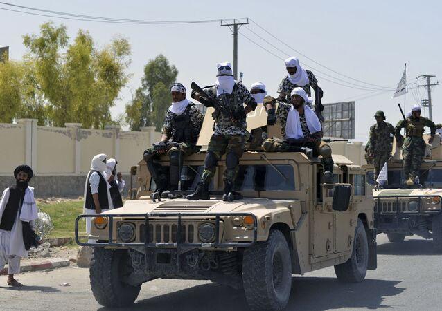 Các chiến binh Taliban trên đỉnh xe Humvee diễu hành dọc theo con đường để ăn mừng sau khi Mỹ rút hết quân khỏi Afghanistan, tại Kandahar vào ngày 1 tháng 9 năm 2021 sau khi quân đội Taliban tiếp quản đất nước