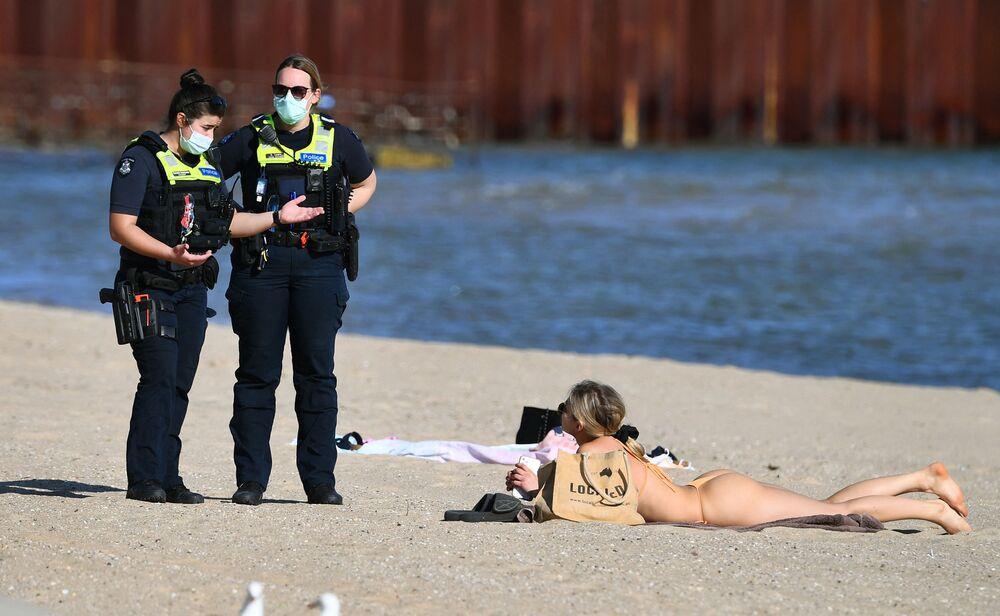 Cảnh sát nói chuyện với người phụ nữ tắm nắng trên bãi biển St Kilda ở Melbourne trong quá trình cách ly