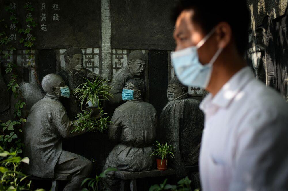 Người đàn ông đi qua các bức tượng đeo khẩu trang bên ngoài một nhà hàng ở Bắc Kinh