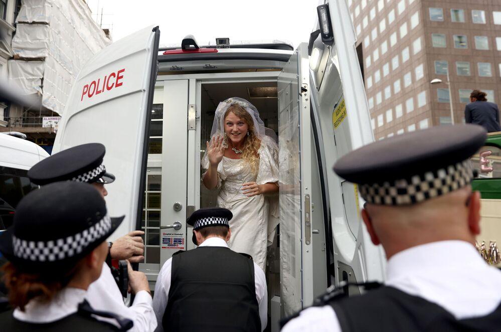 Một nhà hoạt động mặc váy cưới ngồi trong xe cảnh sát trong cuộc biểu tình Extinction Rebellion ở London, Vương quốc Anh