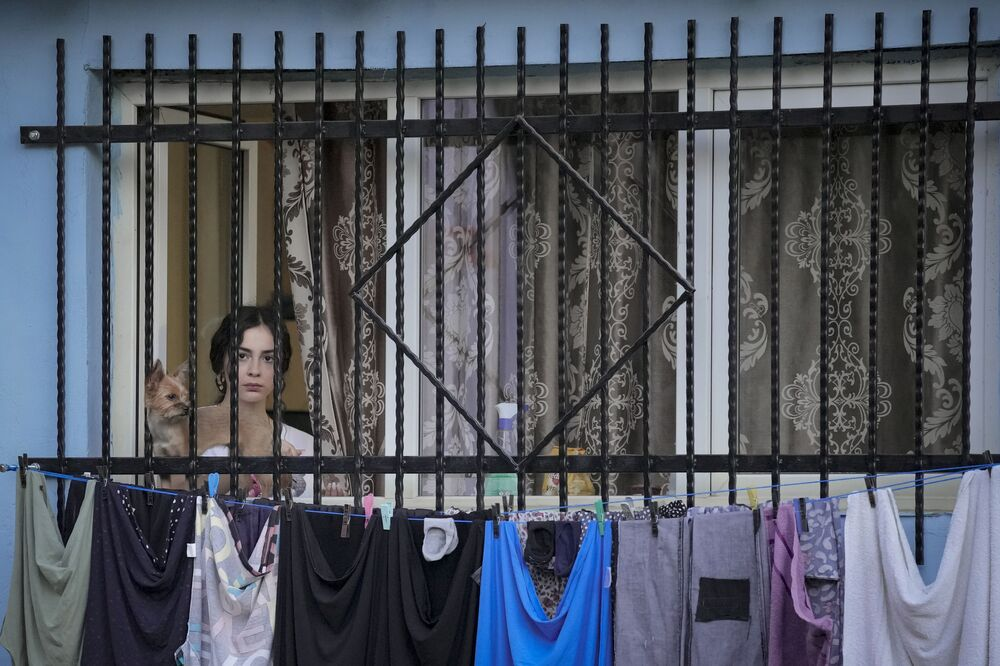 Người phụ nữ sau cửa sổ xem buổi biểu diễn ngoài trời ở Bucharest, Romania