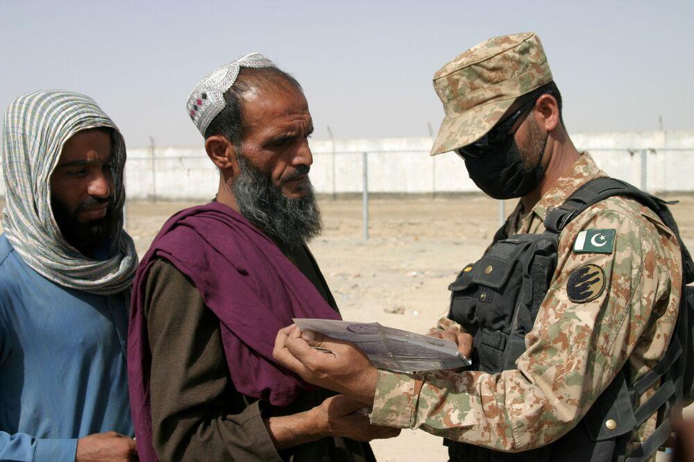 Người lính Pakistan kiểm tra giấy tờ của những người đến từ Afghanistan tại trạm kiểm soát Cổng Tình bạn ở Chaman, thị trấn biên giới Pakistan-Afghanistan, Pakistan