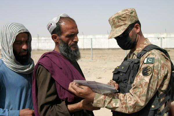 Người lính Pakistan kiểm tra giấy tờ của những người đến từ Afghanistan tại trạm kiểm soát Cổng Tình bạn ở Chaman, thị trấn biên giới Pakistan-Afghanistan, Pakistan - Sputnik Việt Nam