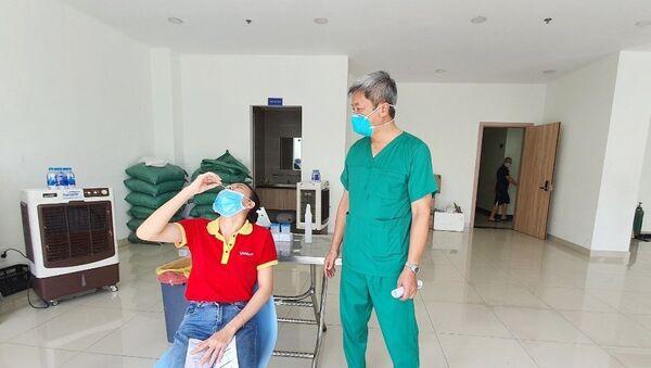 Thứ trưởng Bộ Y tế Nguyễn Trường Sơn quan sát việc hướng dẫn người dân tự xét nghiệm nhanh tại nhà. - Sputnik Việt Nam