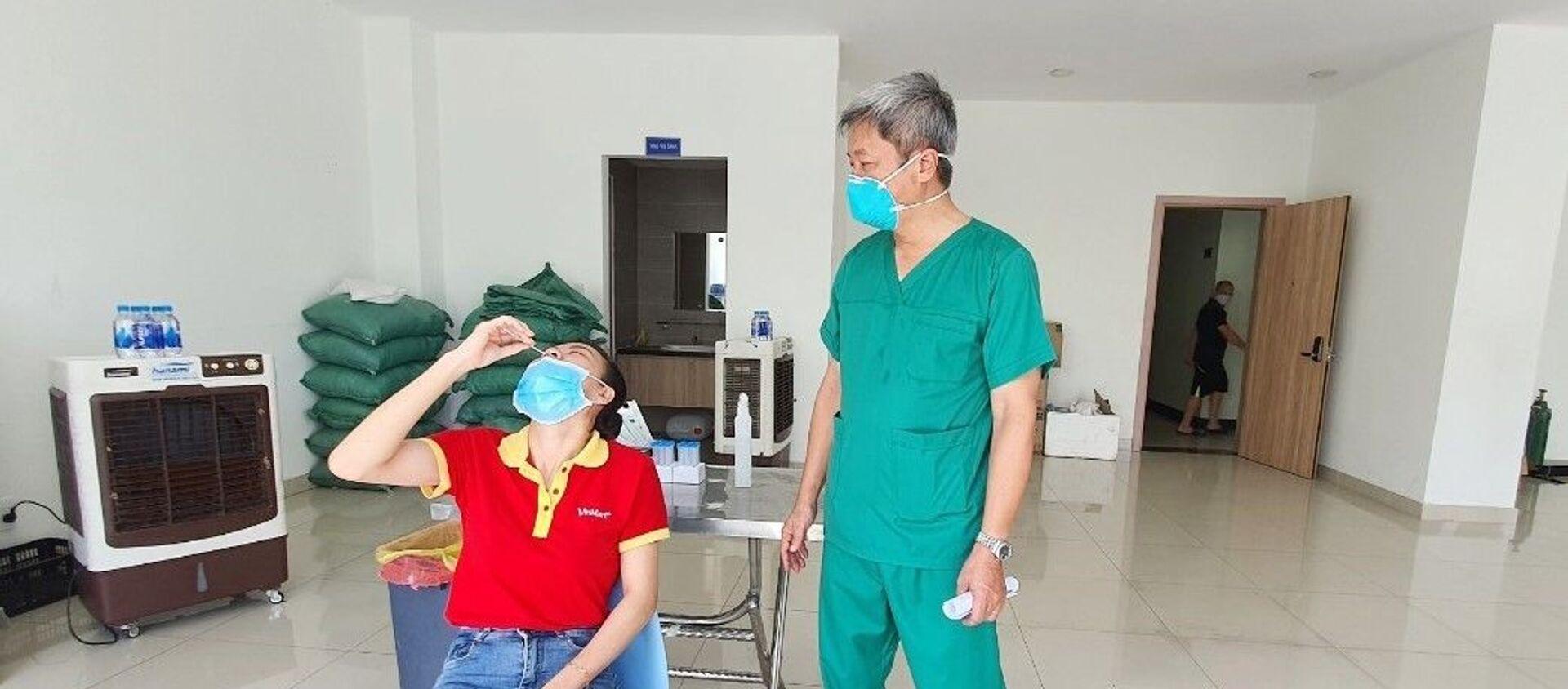 Thứ trưởng Bộ Y tế Nguyễn Trường Sơn quan sát việc hướng dẫn người dân tự xét nghiệm nhanh tại nhà. - Sputnik Việt Nam, 1920, 05.09.2021