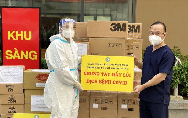 Sư cô Thích Nữ Huệ Đức, Phó Thư ký Phân ban Ni giới Trung ương (trái) trao tượng trưng số vật tư y tế tặng Bệnh viện Dã chiến số 10 (thành phố Thủ Đức), Thành phố Hồ Chí Minh. - Sputnik Việt Nam