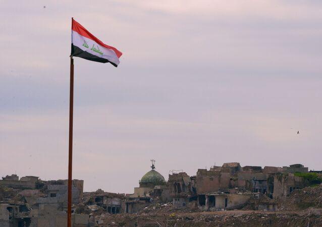 Lá cờ Iraq trên nền những tòa nhà bị phá hủy ở Mosul