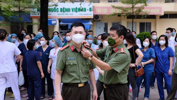 Tranh thủ chỉnh trang trang phục cho đồng đội trước giờ xuất phát lên đường vào tâm dịch TP Hồ Chí Minh. - Sputnik Việt Nam