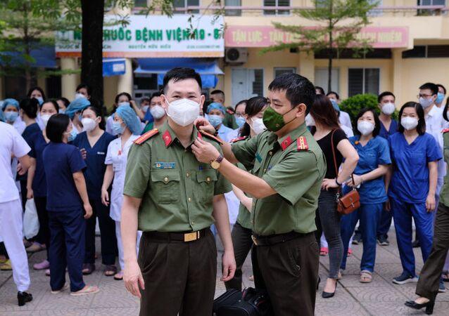 Tranh thủ chỉnh trang trang phục cho đồng đội trước giờ xuất phát lên đường vào tâm dịch TP Hồ Chí Minh.