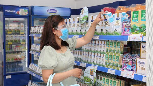 Khách hàng đứng bên quầy bán sản phẩm của Công ty Sữa Việt Nam Vinamilk trong siêu thị - Sputnik Việt Nam
