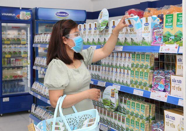 Khách hàng đứng bên quầy bán sản phẩm của Công ty Sữa Việt Nam Vinamilk trong siêu thị