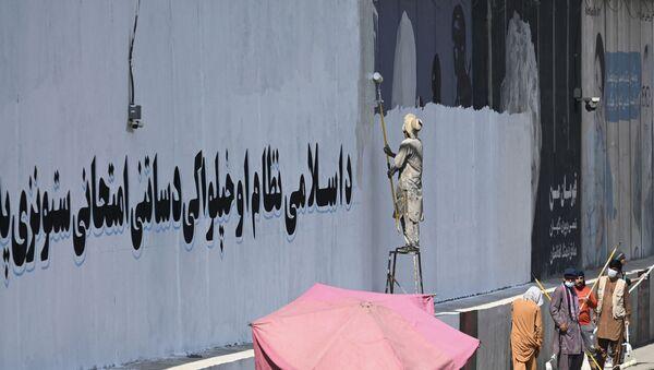 Một người Afghanistan đang phủ sơn để xóa tác phẩm của nhóm sáng tạo người Afghanistan ArtLords - Sputnik Việt Nam