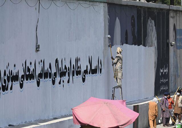Một người Afghanistan đang phủ sơn để xóa tác phẩm của nhóm sáng tạo người Afghanistan ArtLords
