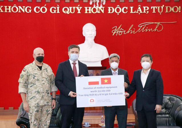 Đại sứ Ba Lan tại Việt Nam Wojciech Gerwel (thứ hai, từ trái sang) trao tượng trưng số trang thiết bị, vật tư y tế do Chính phủ Ba Lan tặng Việt Nam cho ông Nguyễn Trường Sơn, Thứ trưởng Bộ Y tế (thứ hai, từ phải sang) và ông Dương Anh Đức, Phó Chủ tịch UBND TP Hồ Chí Minh (ngoài cùng bên phải)
