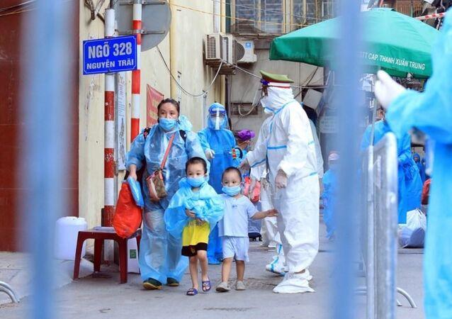 Trẻ em theo gia đình di chuyển đến khu cách ly.