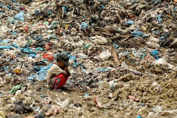 Con trai của một công nhân thu gom rác nghỉ ngơi trong khi người cha tìm kiếm đồ để bán lại tại một bãi rác ở Alue Liem, Lhokseumawe  - Sputnik Việt Nam