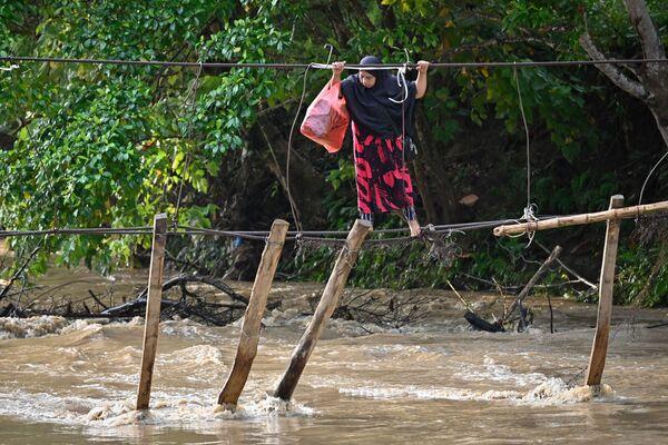 Người phụ nữ vượt qua cây cầu bị lũ phá hủy ở Nam Sulawesi, Indonesia - Sputnik Việt Nam