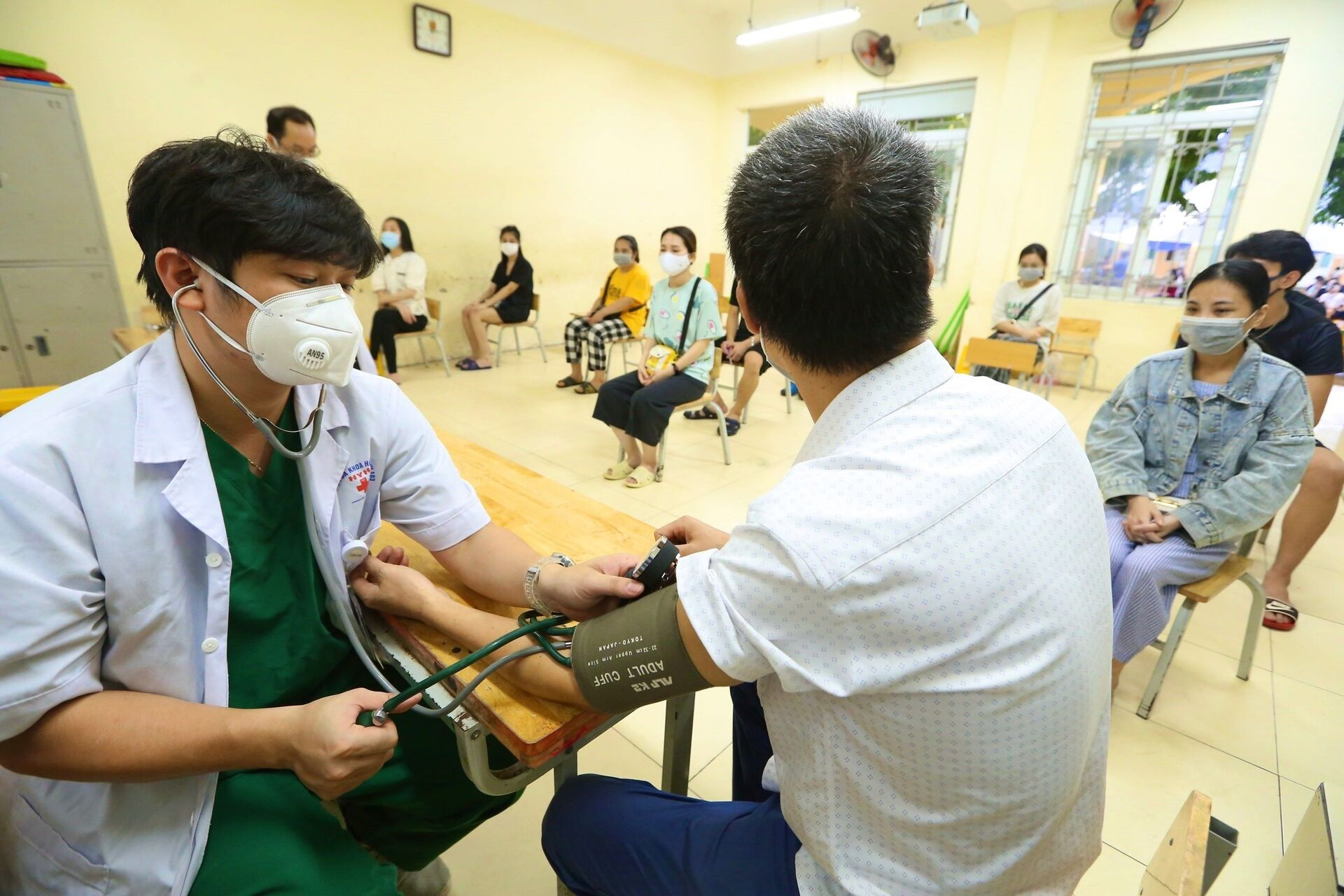 Bác sĩ Bùi Vũ Giang - Bệnh viện hữu nghị Quốc tế Hà Nội đo kiểm tra huyết áp cho người dân phường Mễ Trì trước khi tiêm, sáng 14/9 - Sputnik Việt Nam, 1920, 05.10.2021