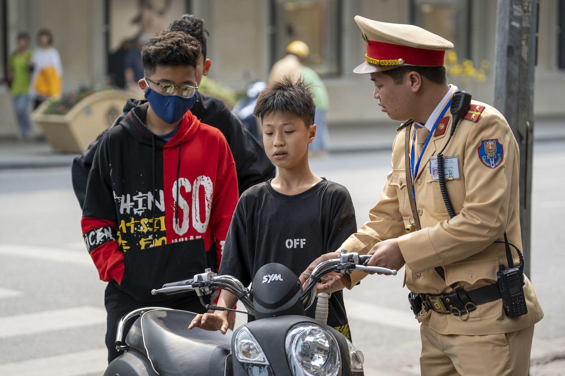 Cảnh sát Việt Nam chặn một cậu bé điều khiển xe máy vì vi phạm luật lệ giao thông trên phố cổ Hà Nội, Việt Nam. - Sputnik Việt Nam, 1920, 05.10.2021