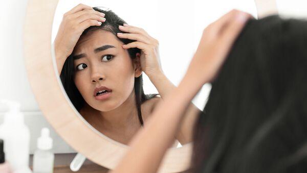 Cô gái đang ngắm mái tóc của mình trước gương - Sputnik Việt Nam